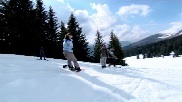vídeos de stock, filmes e b-roll de medium shot pan men and women snowboarding downhill / morzine, france - roupa de esqui