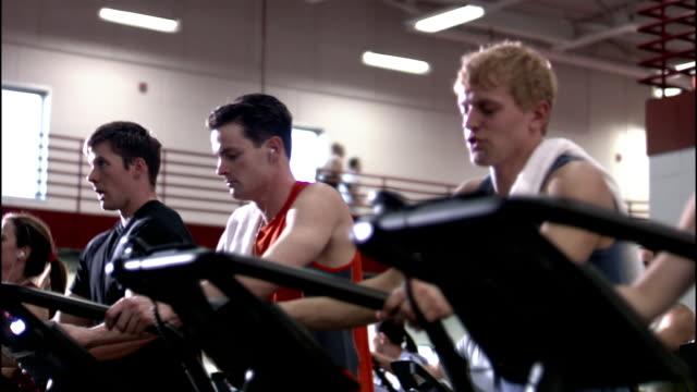 medium shot pan men and women using elliptical trainers at gym - ウィスコンシン州アップルトン点の映像素材/bロール