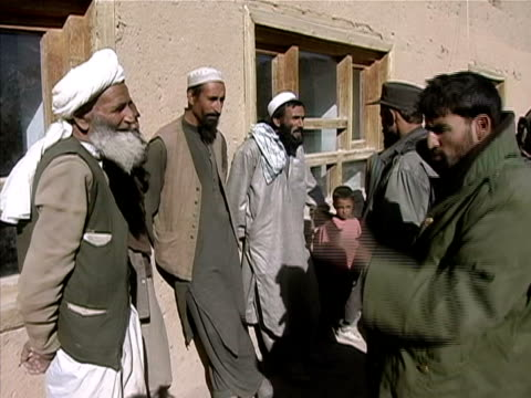 medium shot pan men being questioned by soldiers in village/ zoom in men's faces/ afghanistan - kufi stock videos & royalty-free footage