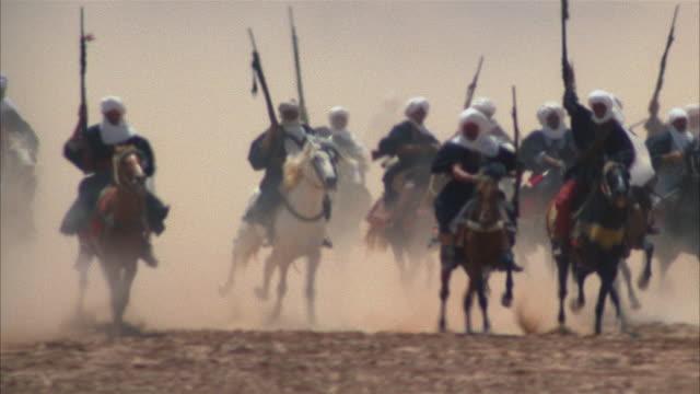 vídeos de stock e filmes b-roll de medium shot pan men in turbans riding on horseback across the desert and holding guns - grupo grande de animais