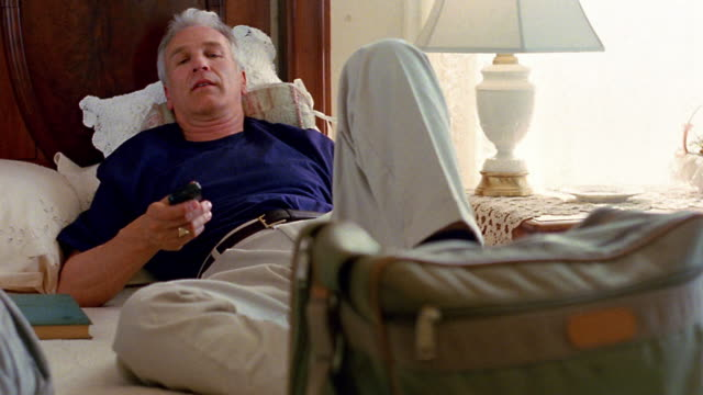 Medium shot pan middle age man lying on bed using remote control and watching television off-screen