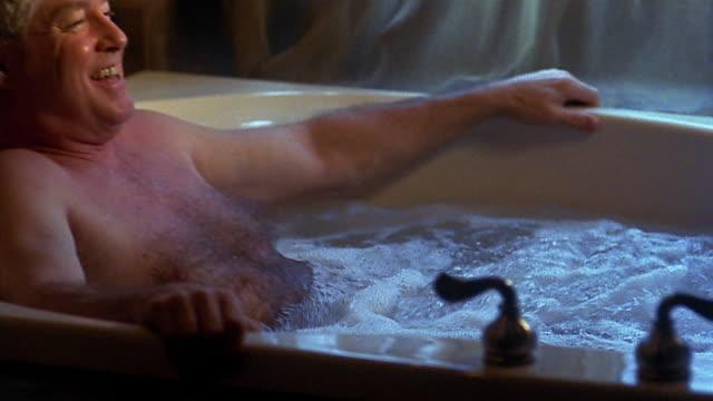 medium shot pan middle aged man leaning back in hot tub - ため息点の映像素材/bロール
