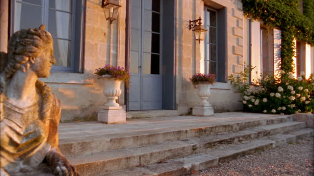Medium shot pan of statue and flower urns+ bushes near front steps of chateau / France