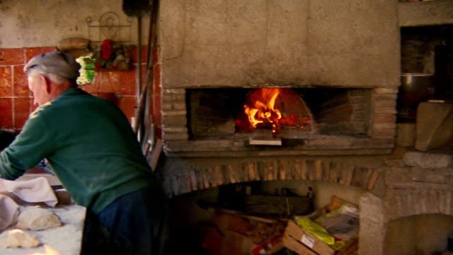 medium shot pan outdoor kitchen with brick oven and senior man in hat kneading dough / provence, france - hearth oven stock videos & royalty-free footage