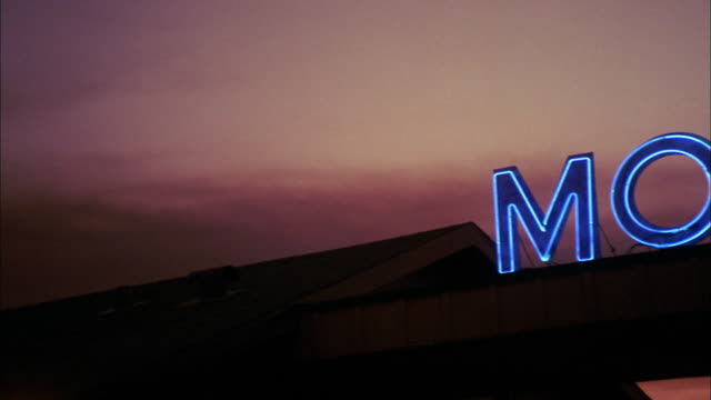 medium shot pan over neon motel and office sign - motel stock videos and b-roll footage