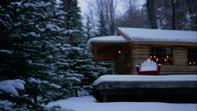 medium shot pan over snowy pine trees and wood ranch home w/deck / colorado - colorado stock videos and b-roll footage