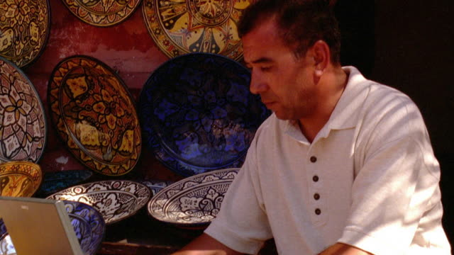 Medium shot pan past decorated dishes on wall to man at laptop / Morocco