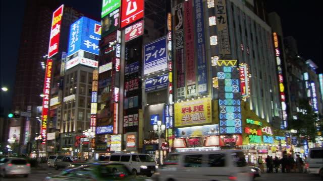 Medium shot pan pedestrians and traffic on neon-lit Shinjuku street at night / Tokyo, Japan
