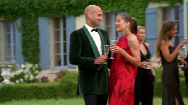 medium shot pan people wearing formalwear at outdoor party / france - formal stock videos & royalty-free footage