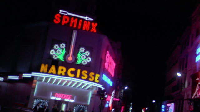 Medium shot pan 'Pigalle' to 'Narcisse' to 'Eve' neon adult nightclub signs at night / Paris