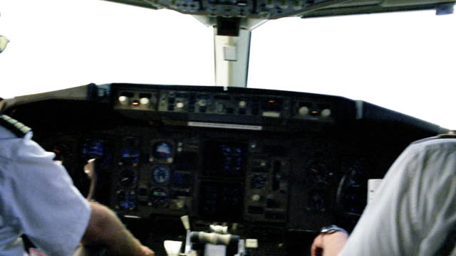 Medium shot pan pilots in cockpit of airplane