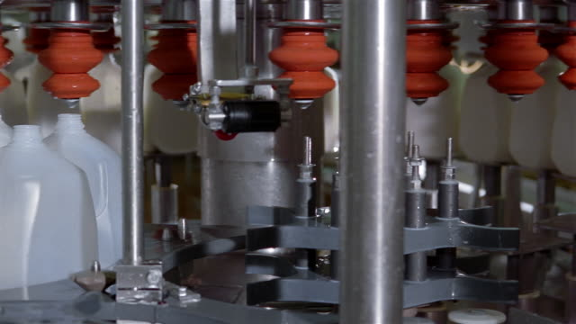 medium shot pan plastic jugs being filled with milk and sealed at dairy factory - milk jug stock videos & royalty-free footage