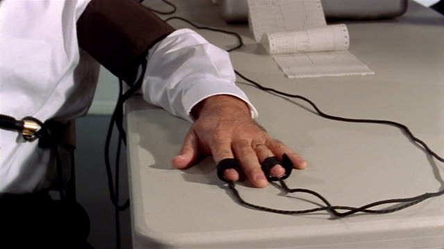 Medium shot pan polygraph machine to man taking lie detector test