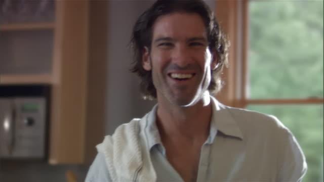 medium shot pan portrait of man smiling in kitchen - only mature men stock videos & royalty-free footage