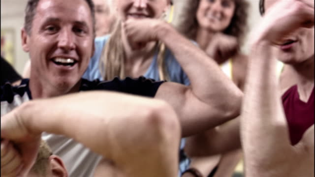 stockvideo's en b-roll-footage met medium shot pan portrait of men and women flexing muscles and posing in exercise class / smiling and looking at camera - bicep