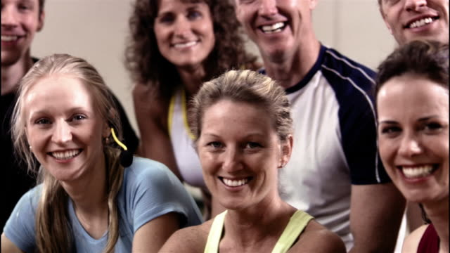 medium shot pan portrait of men and women in exercise class / smiling and looking at camera - ウィスコンシン州アップルトン点の映像素材/bロール