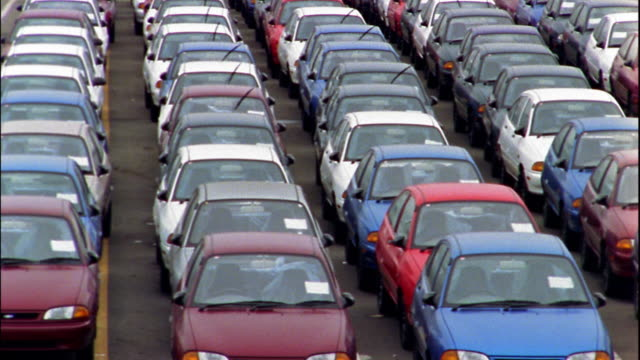 medium shot pan rows of new cars parked in lot - londonalight stock videos and b-roll footage