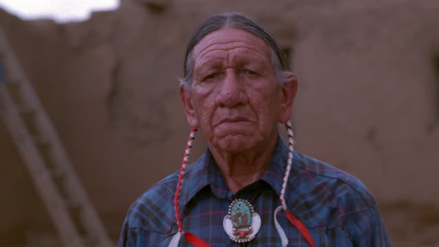 medium shot pan senior native american man posing / taos, new mexico - ネイティブアメリカン点の映像素材/bロール