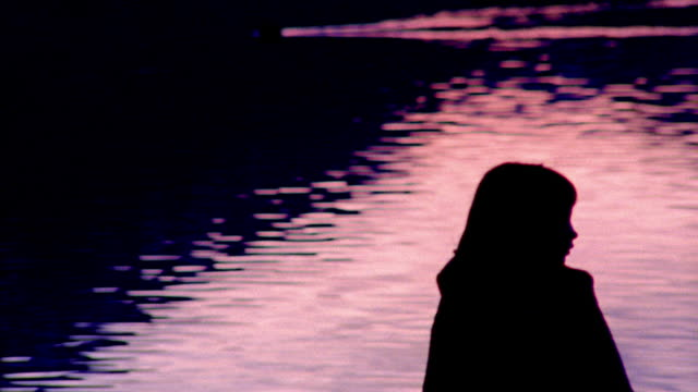 medium shot pan silhouette of girl in cape standing on edge of dock looking over lake / fussen, germany - jetty stock videos & royalty-free footage