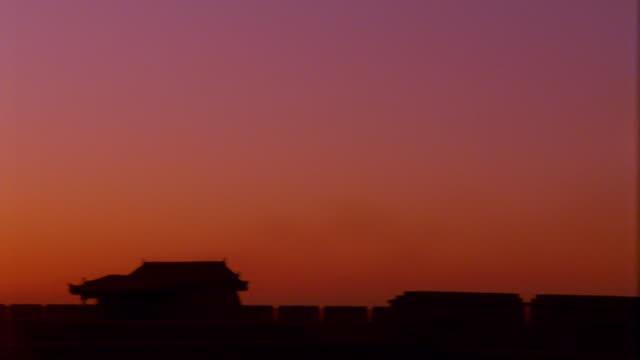 medium shot pan silhouette of pagodas at fort jiayuguan with sunset/rise in background / gobi desert, china - kinesiska muren bildbanksvideor och videomaterial från bakom kulisserna