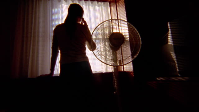 medium shot pan silhouetted woman talking on cell phone at window next to fan - household fixture stock videos and b-roll footage