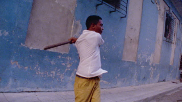 medium shot pan slow motion hispanic boy swinging stick at ball in street baseball game / havana, cuba - kleine personengruppe stock-videos und b-roll-filmmaterial