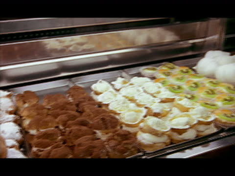 medium shot pan tarts, cannolis and other italian pastries on display - breitwandformat stock-videos und b-roll-filmmaterial
