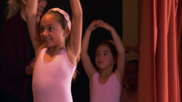 medium shot pan teacher guiding young girls wearing leotards onto stage / girls twirling around with arms up and smiling - pacific islander teacher stock videos & royalty-free footage