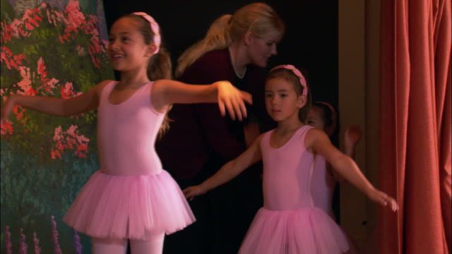 Medium shot pan teacher guiding young girls wearing leotards onto stage / girls holding arms out as they dance across stage