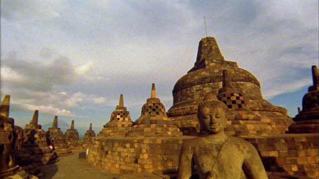 Medium shot pan temple and Buddhist statue of Borobudur / Java, Indonesia