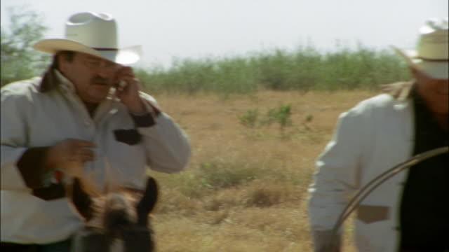Medium shot pan three cowboys riding side by side on horseback/ cowboy on cellphone/ Edinburg, Texas