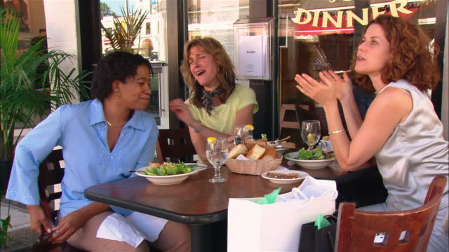 Medium shot pan three women eating and talking at outdoor cafe/ Westfield, New Jersey