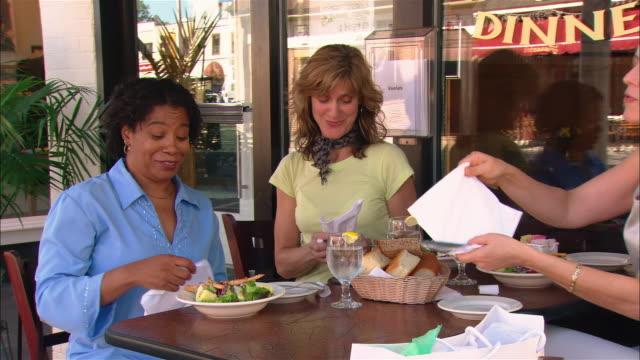 Medium shot pan three women preparing to eat at outdoor cafe/ Westfield, New Jersey