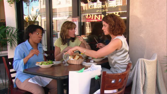 Medium shot pan three women talking and eating at outdoor cafe/ Westfield, New Jersey