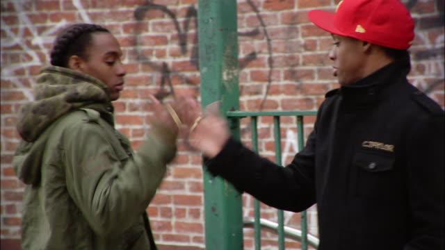 medium shot pan two brothers giving each other street handshakes near subway sign / new york city, new york, usa - スウィッシュパン点の映像素材/bロール