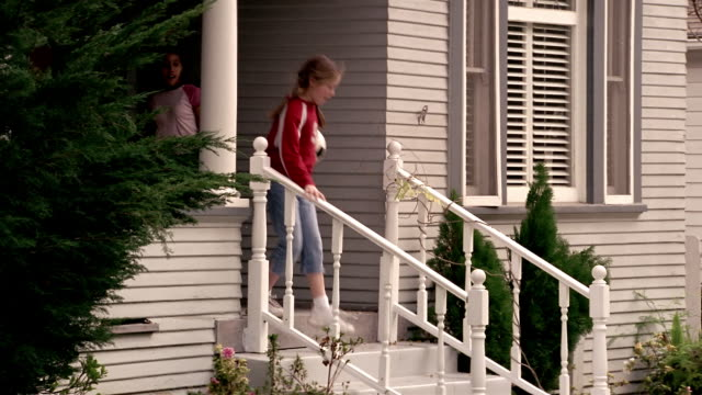 Medium shot pan two girls leaving house / walking down steps carrying soccer ball and baseball glove