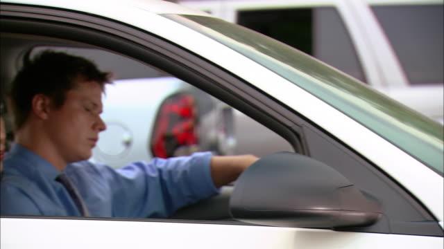 medium shot pan two men and two men carpooling stuck in traffic - trafikstockning bildbanksvideor och videomaterial från bakom kulisserna
