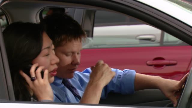 Medium shot pan two men and two women carpooling to work / stuck in traffic