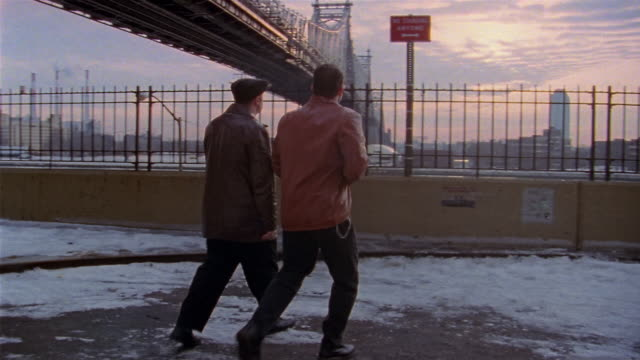 Medium shot pan two mobsters stopping to look at skyline from bridge and walking off