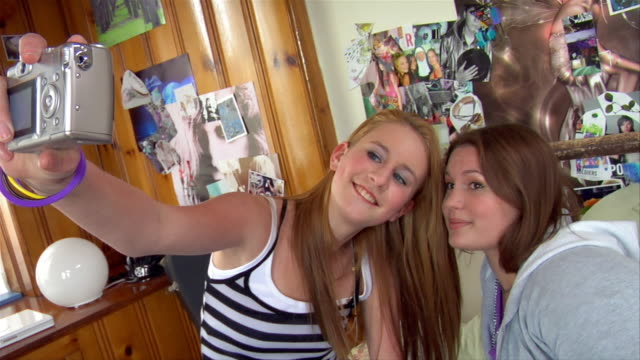 medium shot pan two teen girls taking self portrait with digital camera and then one girl taking photo of friend in bedroom / brooklyn, new york, usa - スウィッシュパン点の映像素材/bロール