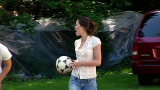 medium shot pan two women and man tossing soccer ball around/ roxbury, new york - 男性と複数の女性点の映像素材/bロール