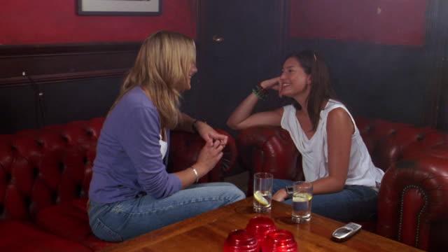 vídeos de stock e filmes b-roll de medium shot pan two young women sitting on sofa's in bar and talking / man sitting by them + talking - sentar se