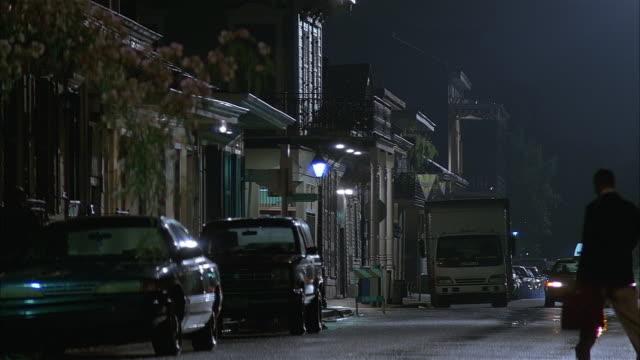 medium shot pan view of man walking to his car and taxi driving down street / louisiana - louisiana stock videos & royalty-free footage