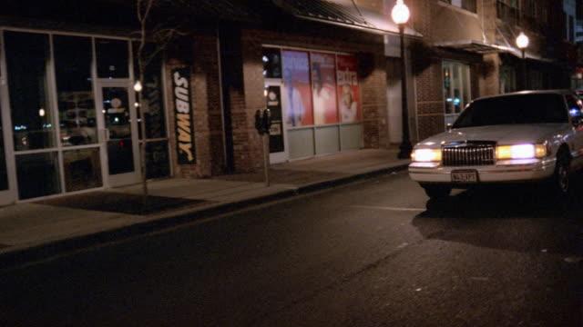medium shot pan white limousine on city street at night / passing by camera - リムジン点の映像素材/bロール
