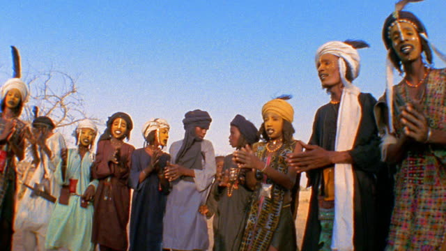 Medium shot pan Wodaabe people in traditional dress and face paint clapping at outdoor wedding / Niger