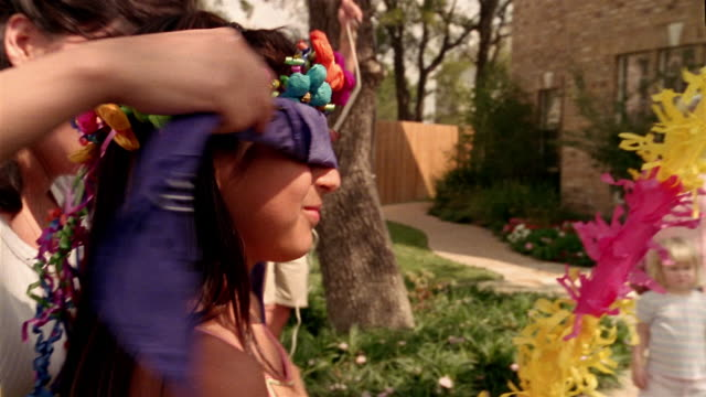 medium shot pan woman blindfolding little girl / girl swinging at pinata - blindfold stock videos & royalty-free footage