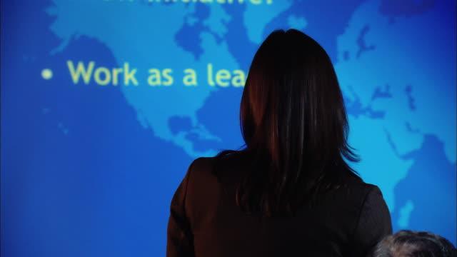 medium shot pan woman giving presentation in board room/ new york, new york - strategia di vendita video stock e b–roll