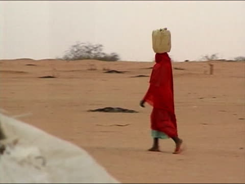 2004 medium shot pan woman in red carrying jug of water on her head / darfur sudan - in den zwanzigern stock-videos und b-roll-filmmaterial