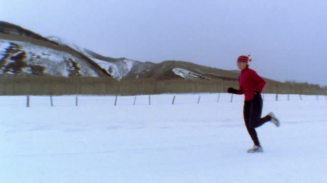 medium shot pan woman jogging on snowy road w/mountains and trees in background / vail, colorado, usa - lycra stock videos & royalty-free footage