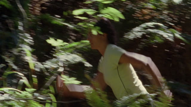 Medium shot pan woman running up hill on forest trail/ California